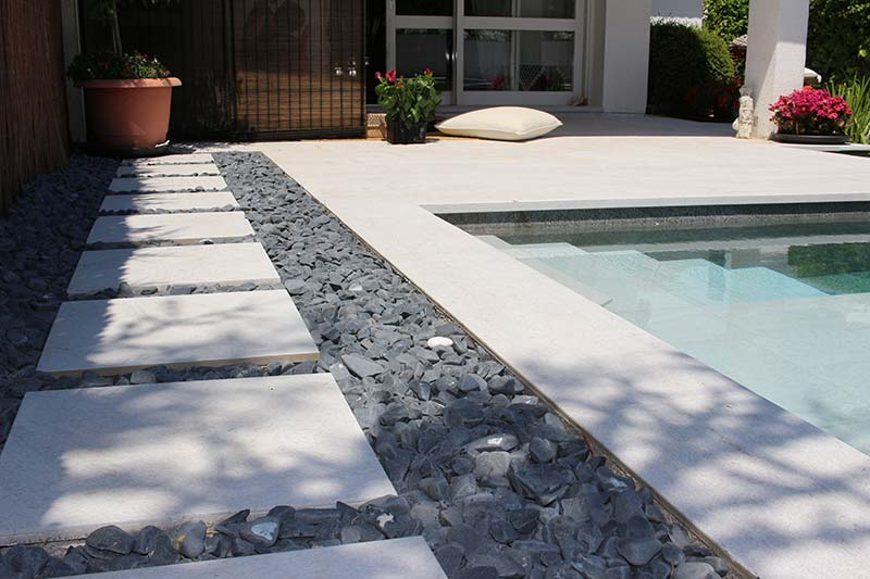 Black and white pool with porcelain pieces on pebbles