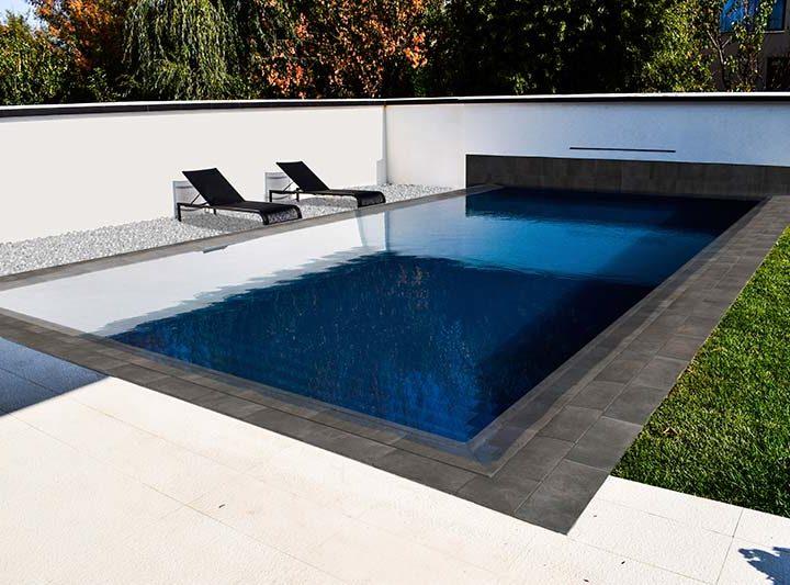 La elegancia de los colores oscuros como revestimiento del vaso de la piscina