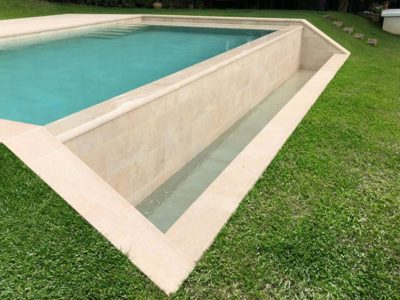 Overflowing pool with Vintage Bone porcelain tiles by Rosa Gres