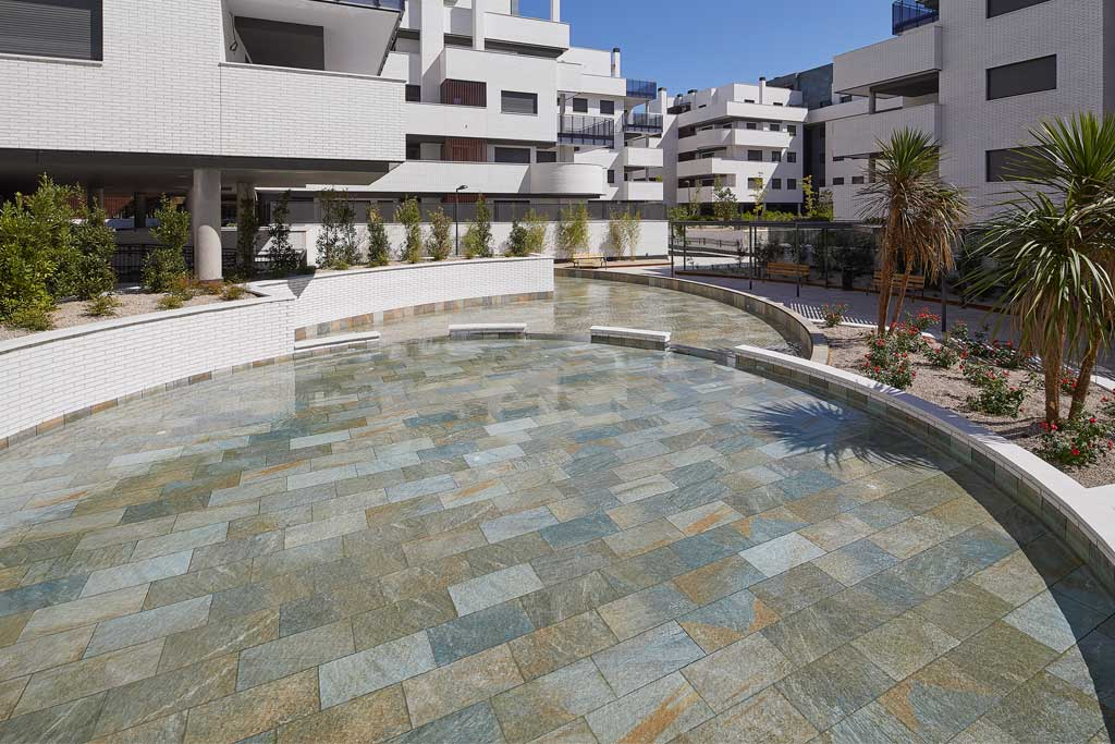 Swimming pool with curves in Serena Mix porcelain stoneware. El Bosque., Madrid | Rosa Gres