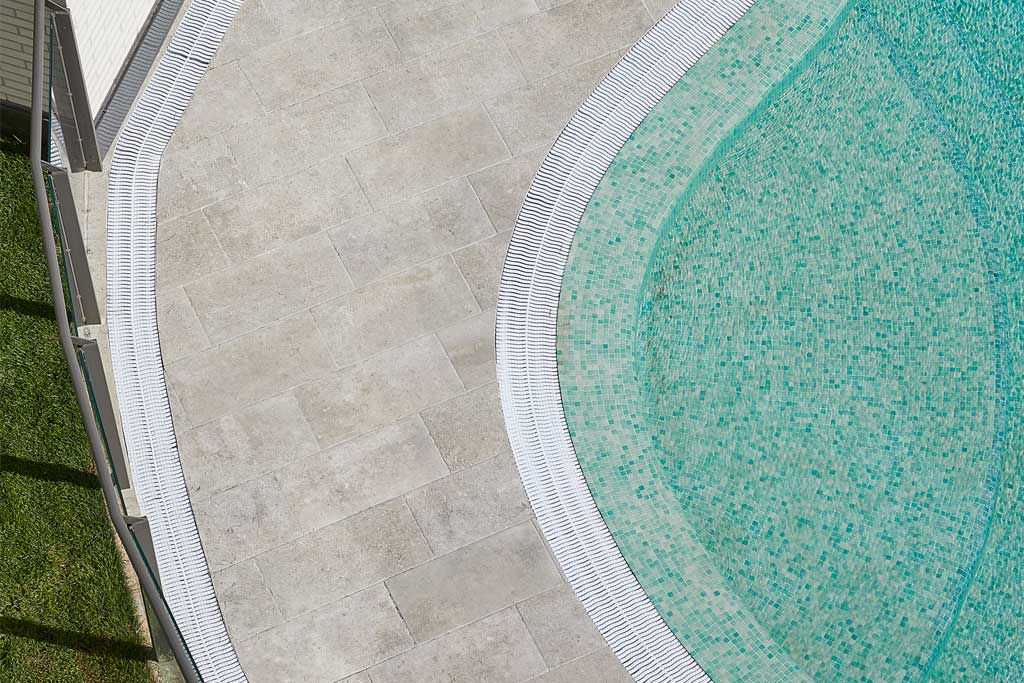 Detail of Mistery Grey porcelain stoneware pavement on curved pool. Spain | Rosa Gres