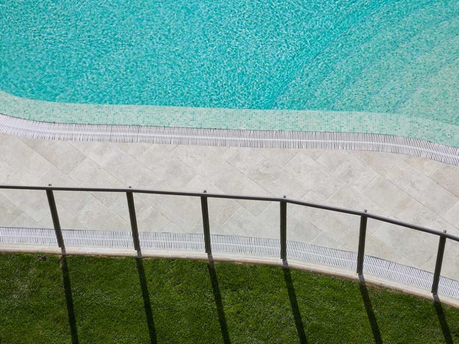 Detail of overflowing pool pavement with curves in Mistery Grey porcelain stoneware. Spain | Rosa Gres