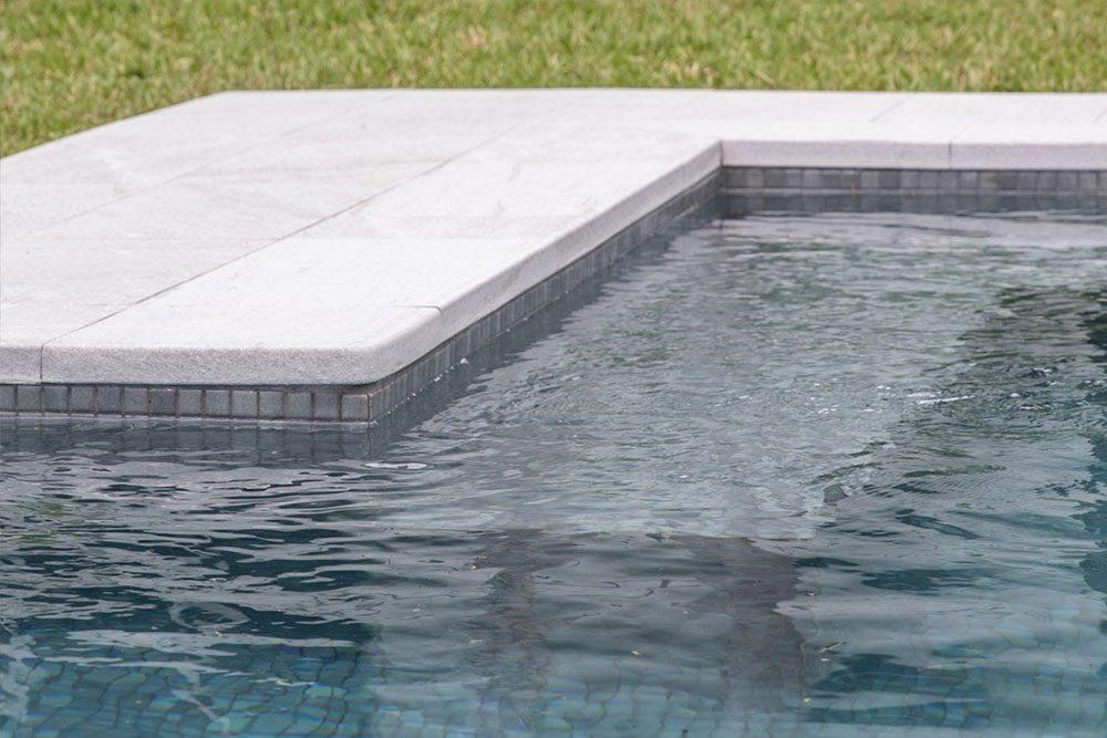 Borde en L de piscina privada en gres porcelánico Serena Bianco | Rosa Gres