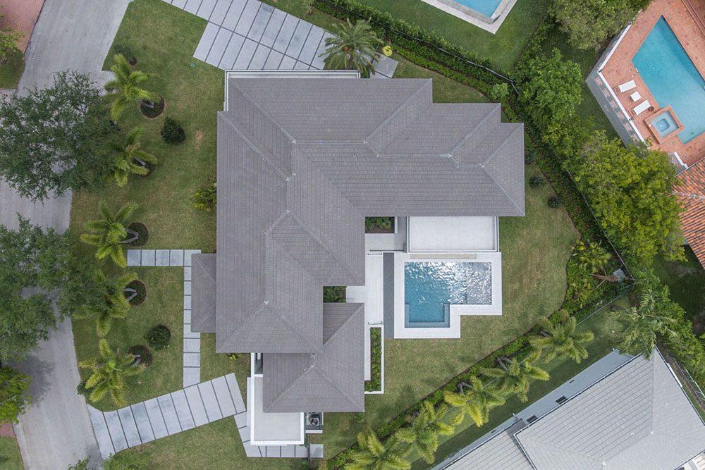 Vista area de terrazas y piscina privada en gres porcelánico Serena Bianco | Rosa Gres