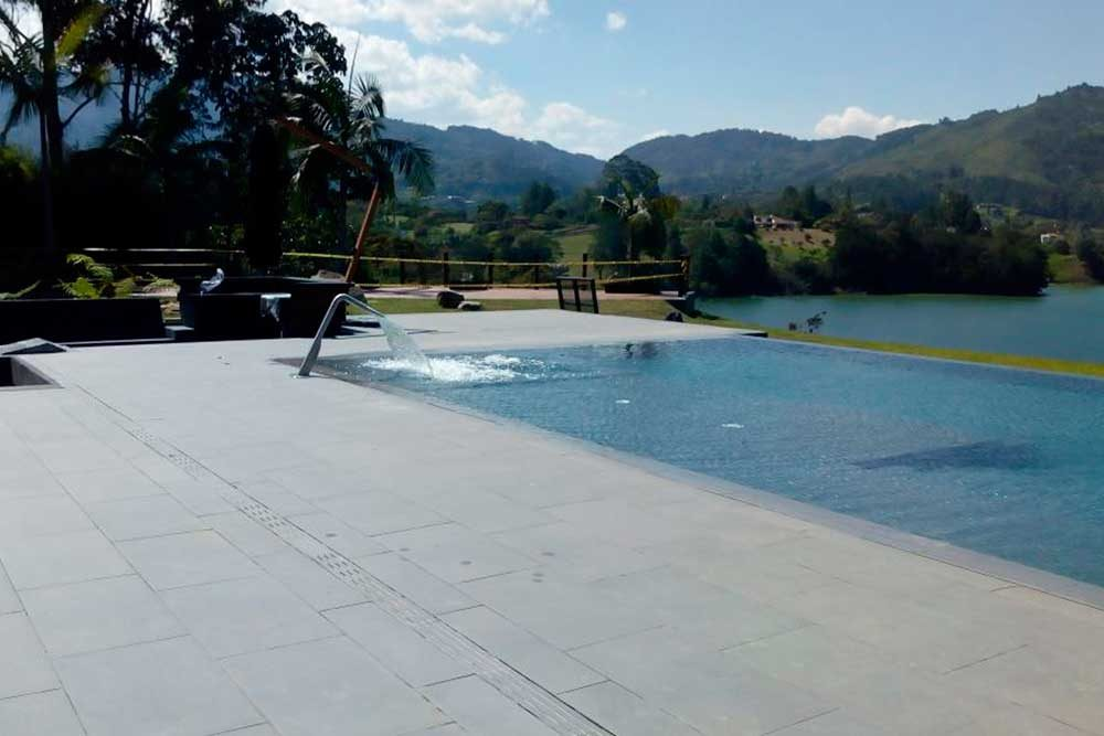 Piscina privada. Borde piscina infinity y asoleadero en gres porcelánico Tao Grey. Colombia | Rosa Gres