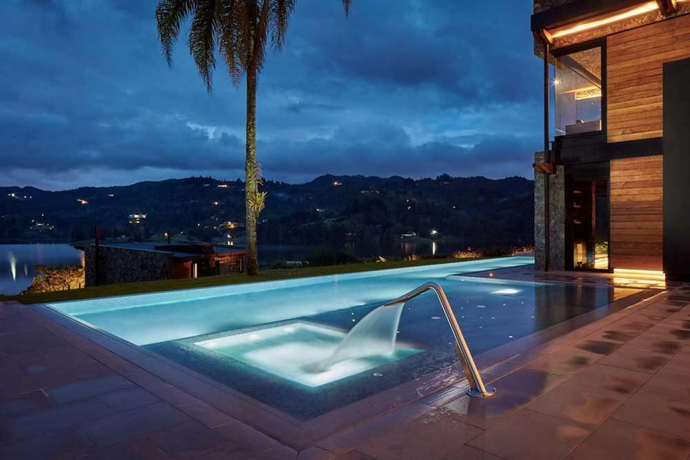 Piscina privada. Iluminación piscina infinity y spa en gres porcelánico Tao Grey. Colombia | Rosa Gres